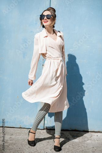 Woman portrait on the blue background outdoors