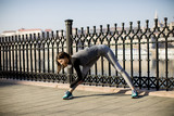 Young woman practices stretching after jogging outdoor