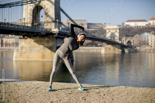 Foto Murales Woman in sportswear stretching on Danube river promenade in Budapest