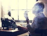 Side view of man smoking pipe while working on typewriter