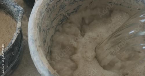 wlewając wodę do betonowego tynku w wiadrze