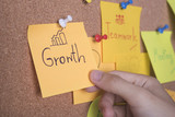 Growth text on sticky note or post is on cork bulletin billboard. - 200736417