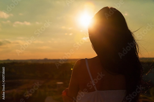 the girl in the rays of the setting sun
