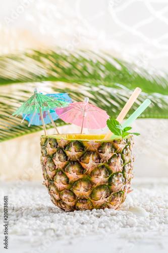 Foto Murales Fresh drink in pineapple on sandy beach on white pebbles
