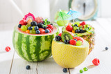 Fruits salad in melon and pineapple on white table