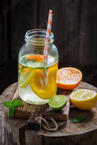 Woda z owoców cytrusowych i liści mięty na starym pniu