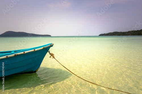 Keuken foto achterwand Tropical strand A blue boat with a rope against calm, turquoise and crystal clear water.