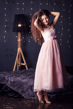 long-haired girl in pink dress in studio on dark background with bokeh. Copy space.