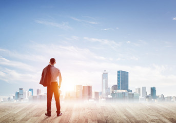 Motivation and inspiration concept with modern cityscape and businessman observing it
