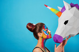 Sideview of pop art portrait of model wearing black opened top. Girl has saturated make up with bright geometrical figures and fancy hairdress. Posing on blue background with pink paper unicorn's head
