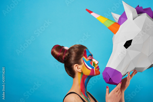 Sideview of pop art portrait of model wearing black opened top. Girl has saturated make up with bright geometrical figures and fancy hairdress. Posing on blue background with pink paper unicorn's head © serhiibobyk