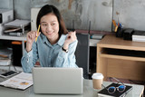 Young asian businesswoman working with laptop computer at office with happy emotion, working at home, office casual lifestyle concept - 200771016
