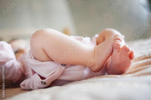 dziecko leży w łóżku z gołymi nogami