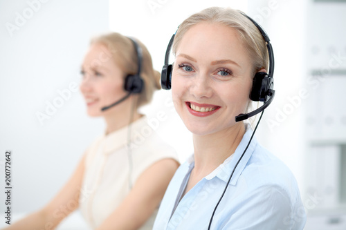 Image of bright call center. Focus on young beautiful woman in a headset - 200772642