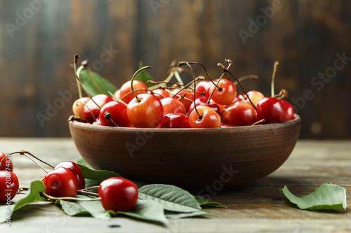 Ripe cherries with leaves on a wooden background