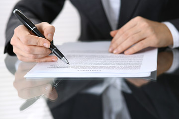 Close-up of female hands with pen over document,  business concept
