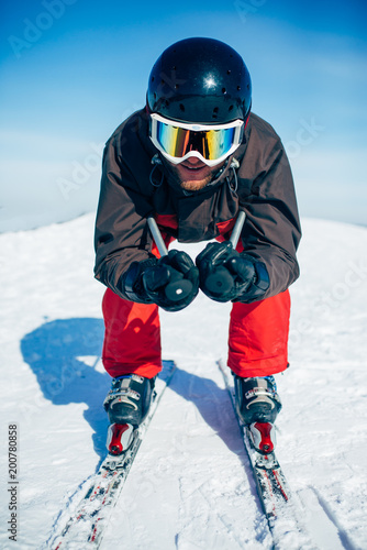Foto Murales Skier racing from the mountain, front view
