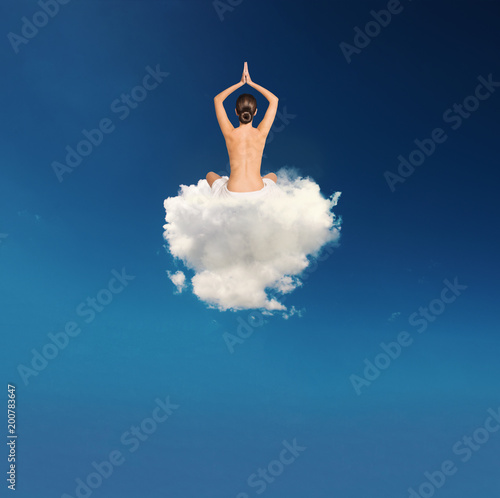 Foto Murales Young girl practices yoga over a cloud