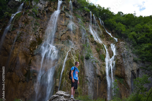 man standing on stone and enjoy view under great waterfall in Plitvice National Park Croatia  - 200786603