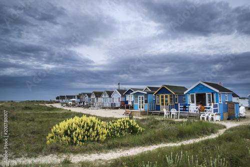 Piękny krajobraz dramatyczny burzowy niebo nad plażowymi budami w trawiastych diunach