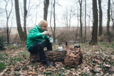 Man with backpack drinking coffee in wild forest. Travel and adventure concept. Landscape photography