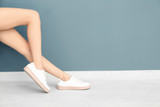 Beautiful woman in stylish shoes near color wall