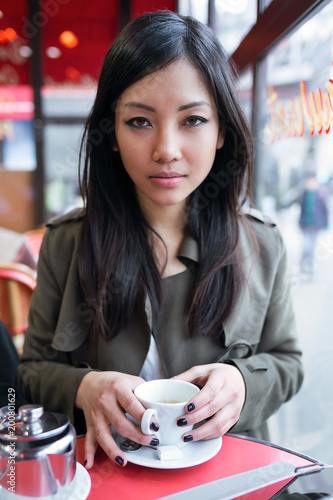 Beautiful young asian woman drinking coffee in the terrace of a coffee shop.