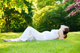 Beautiful pregnant woman relaxing in the spring park - 200805227