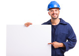 Smiling young worker pointing to a white placard ready for your text or product