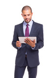 Handsome business man looking to tablet computer, isolated over white background
