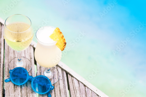 delicious fruit cocktail and white wine with sunglasses on wooden table by the beach