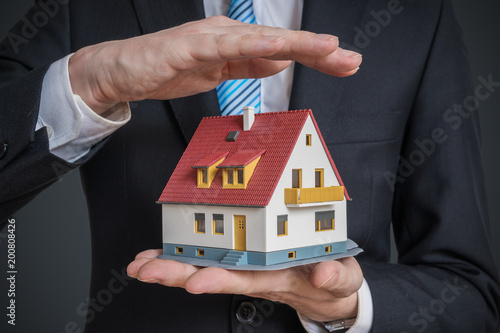 Home insurance concept. Man is holding model of house.