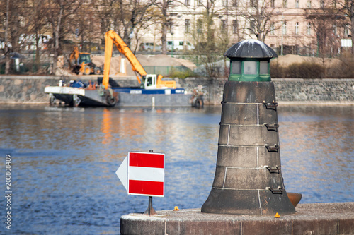 Fotobehang Praag The lighthouse, navigation or orientation landmark built on the riverbank of one of Prague island Zofin. The construction machines at the backgroundm opposite riverbank of Vltava river.