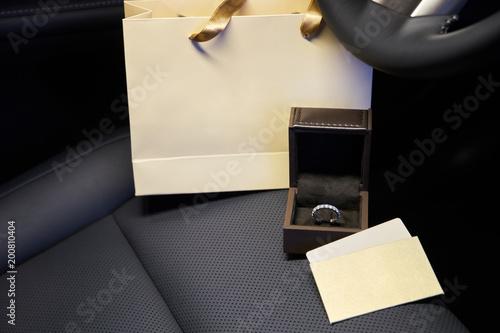 Pierścionki i kolczyki z diamentami w salonie luksusowego samochodu, prezent dla kobiet. Puste karty i torba na zakupy z miejsca kopiowania dla tekstu