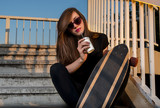 Cool girl long boarder sitting on stairs at sunset and drinking shake  - 200814827