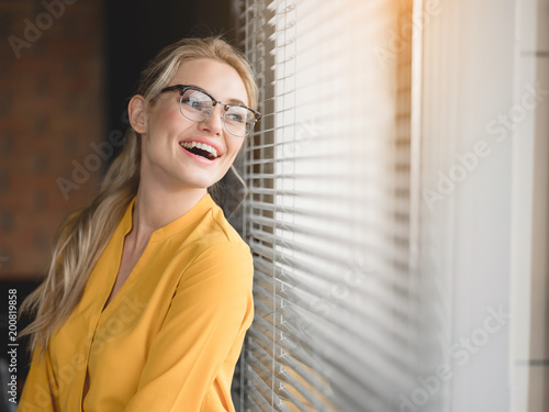Portrait of excited young businesswoman is looking over the window jalousie with enjoyment