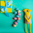 Green background with macaroones gift and yellow toy