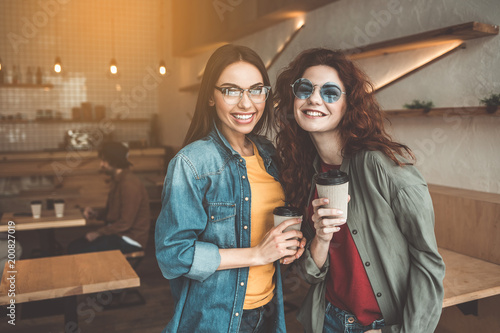 Portrait of joyful two young girls spending free time in cafe. They are standing and smiling while drinking coffee