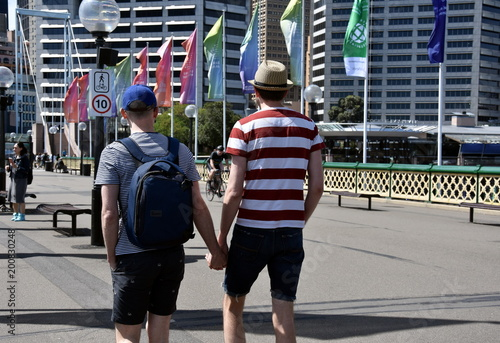 Foto op Aluminium Sydney Homosexual couple holding hands and walking on urban street in Sydney. Gay people LGBT relationship with male partners sharing time together.