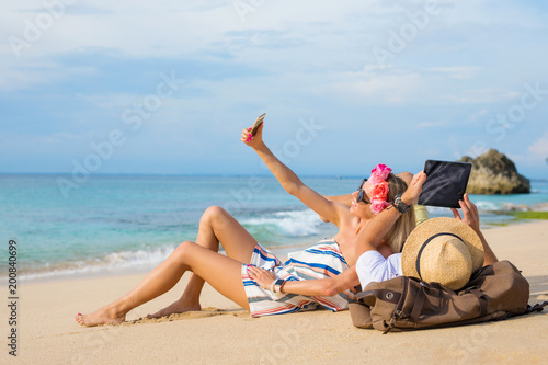 Foto Murales Couple relaxing on the beach and using tech devices