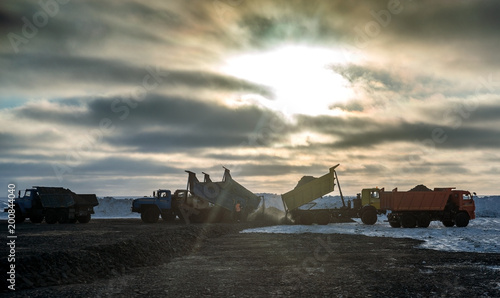 Fotobehang Antarctica Six dump trucks unload gravel during construction in the Arctic. The pre-storm sky and the sun through the clouds..