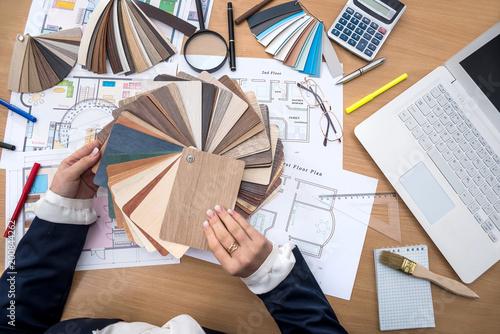 Projektant pracuje w biurze z próbkami kolorów, laptopem i planem budynku