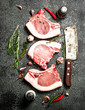 Raw pork steak with a sprig of rosemary and spices.
