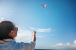 Beautiful young woman launches a kite in the blue sky