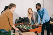 smiling multiethnic business colleagues playing table football in modern office