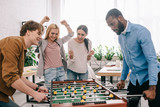 side view of happy multicultural businessmen playing table football in front of celebrating and gesturing female colleagues - 200852454