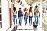 Multi ethnic teenagers friends walking in the school hallway, back view - 200856243