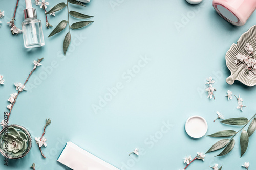 Beauty background with facial cosmetic products, leaves and cherry blossom on pastel blue desktop background. Modern spring skin care layout, top view, flat lay. - 200860275