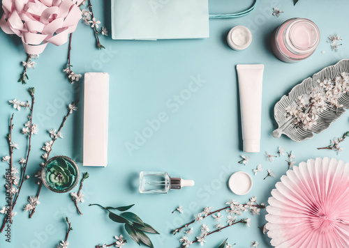 Foto Murales Beauty concept with facial cosmetic products, shopping bag and twigs with cherry blossom on pastel blue desktop background. Modern spring skin care trends, top view, frame, flat lay. Branding mock up