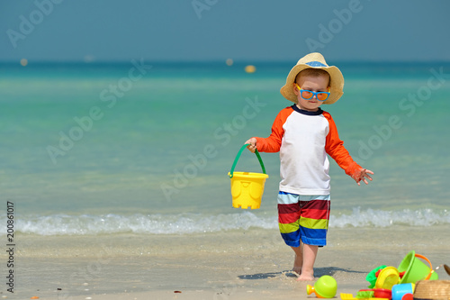 Foto Murales Two year old toddler playing on beach